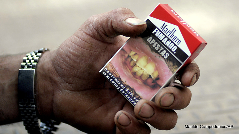 "A man shows his cigarette package covered by a warning that reads in Spanish ""Smoking, you stink,"" top, and ""Smoking causes bad breath"" in Montevideo, Uruguay."